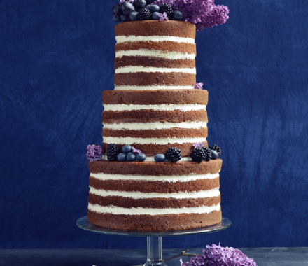 Naked wedding cake with lilacs and blue fruit